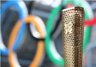Copied from Playback - The London Organising Committee of the Olympic and Paralympic Games (LOCOG) today showcases prototypes of the London 2012 Olympic Torch to be carried by 8,000 inspirational Torchbearers.The winning design connects the London 2012 Olympic Torch Relay to each of the 8,000 Torchbearers and their community. The Torch's triangular, gold-coloured form is perforated by 8,000 circles representing the 8,000 Torchbearers and their stories of personal achievement and/or contribution to their local community which will be celebrated during the London 2012 Olympic Torch Relay.