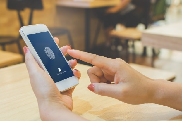 Hand women holding smartphone and scan fingerprint biometric identity for unlock her mobile phone
