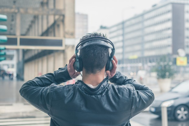 Back view of a young man with headphones posing in the city stre