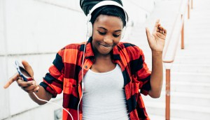 Half lenght of young beautiful afro black woman listening musi with head phones and smart phone hand hold, dancing in the street of the city - dancing, happiness, having fun concept