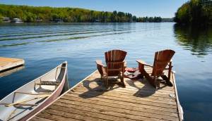 Two,Adirondack,Chairs,On,A,Wooden,Dock,Facing,The,Blue